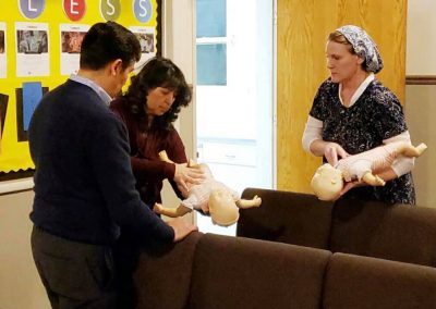 Our teacher, Rabbi John and his wife, Mora practicing what is called 'back blows' and 'chest thrusts' on an unresponsive infant choking victim (manikin).